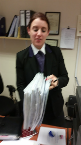 Picture of Hayley a funeral director holding lots of paperwork