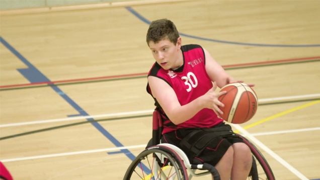 A young man in a wheelchair playing basketball in a sports hall.