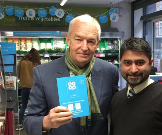 Channel 4 news anchor Jon Snow holding up his Co-op membership card next to a Co-op colleague