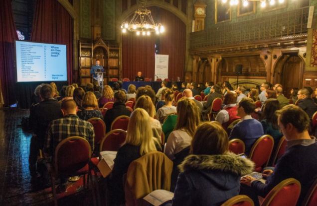 Photograph of hall with attendees and speaker inside Manchester Town Hall
