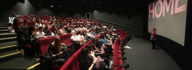 image is from Sunday screening and shows Gemma speaking at the front of a cinema packed with families.
