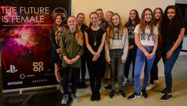 Photograph of the latest graduates from the Girl Geek Academy smiling at the camera next to a poster that says 'The Future is Female'.