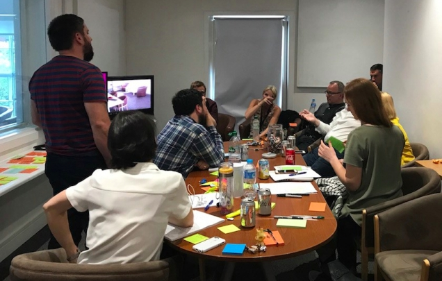 Photograph of a user research session. Shows 10 members of the Electrical discovery team talking about and analysing what they've seen in the user research lab.