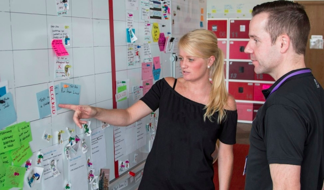 Two colleagues from the Digital team looking at the whiteboard roadmap to see what's coming up in the future.