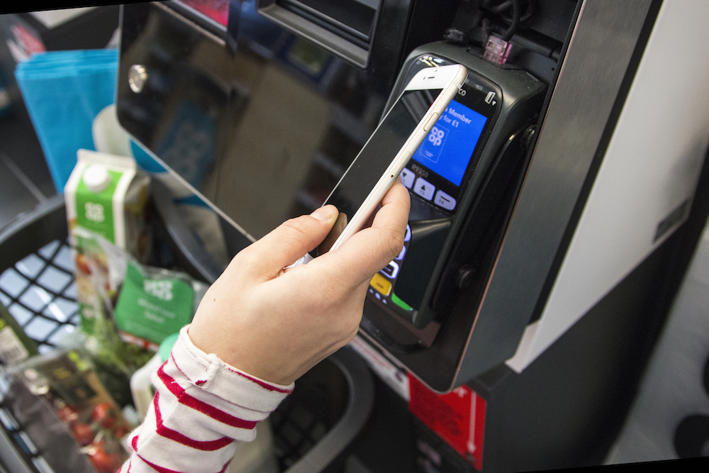 Photograph of member's hand holding phone with membership app at the checkout