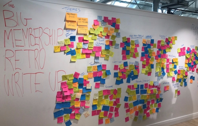 Photograph of a wall with hundreds of post it notes from the mega retro stuck on it. The big membership retro write up is written in red pen on the wall.