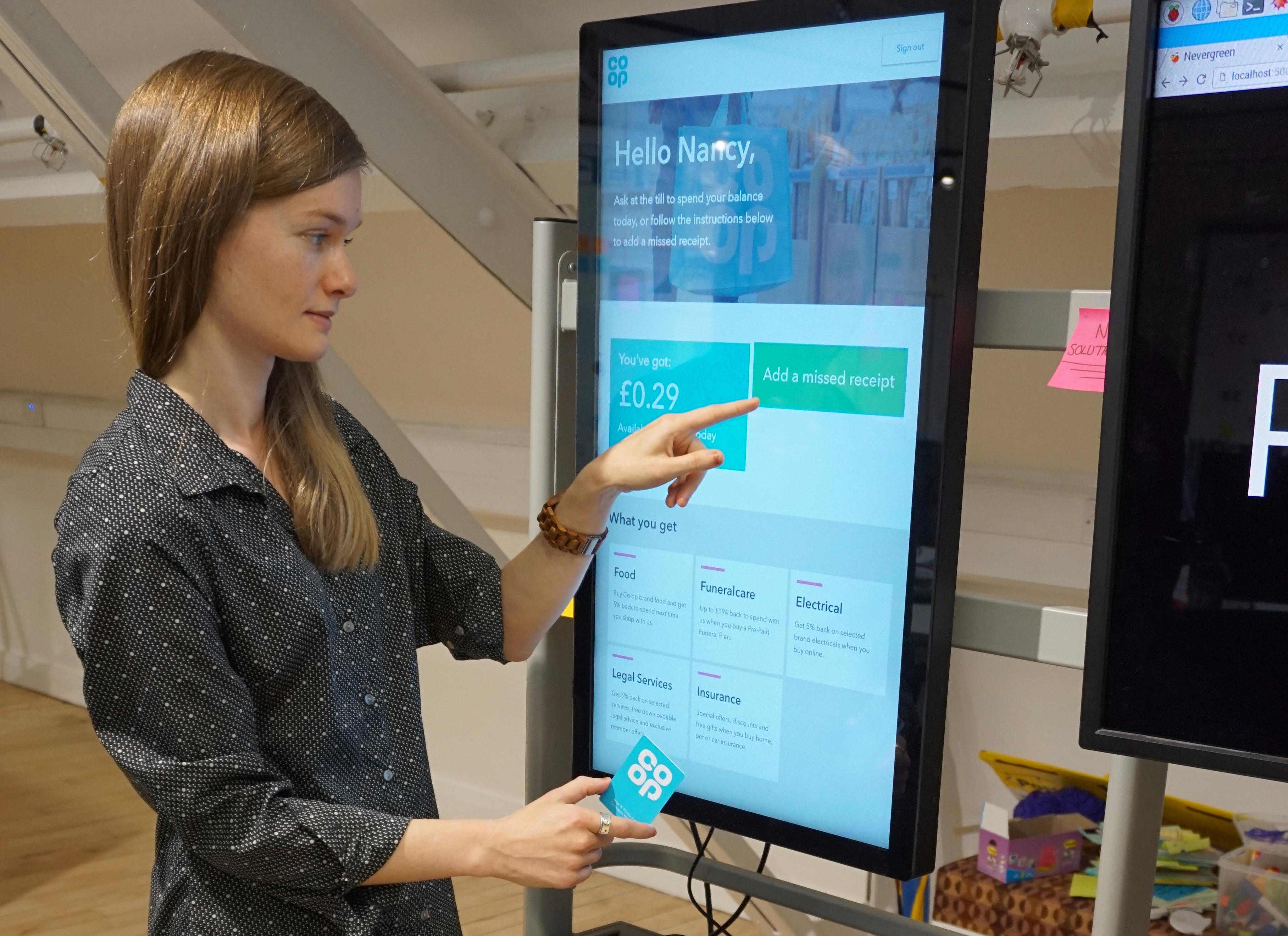 photograph of colleague Nancy using the touchscreen in the office. Touchscreen shows Nancy is signed into her account, she can see her rewards and she can add a missed receipt.