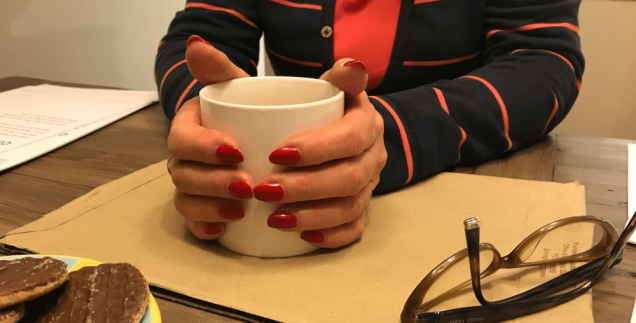 Photograph of hands cupping a mug at a dining table. Glasses in shot as well as a plate of chocolate biscuits.