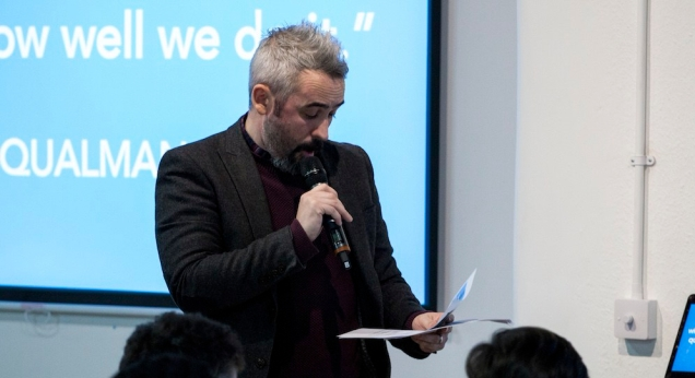 Photograph of Matt Eyre reading from prompt sheet in front of students.