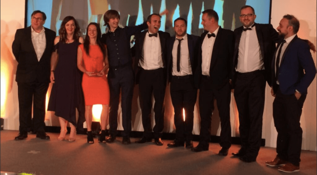 Photograph of the IT service management team stood on stage at an awards ceremony celebrating their award