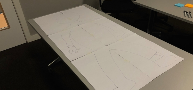 photograph of 'brenda' a outline of a person drawn onto a huge sheet of paper placed on the table for the research dummy run.